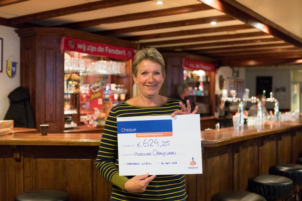 Bestuurslid Riky van der Zande toont blij de cheque die zij zojuist heeft ontvangen.